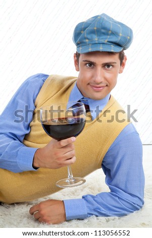Man with large wine glass leaning on rug.