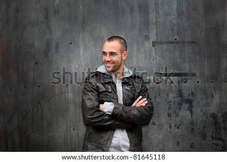 Man with leather jacket standing on metal door - stock photo