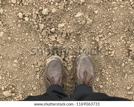 Man with leather shoes on dirty ground #1169063731