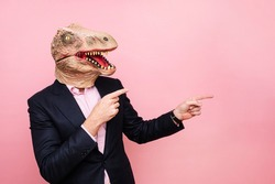 Man with lizard head and pointing fingers to the side.