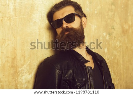 Man with long beard and mustache. Guy with serious face. Biker fashion and beauty. Fashion model on textured wall background. Hipster in leather jacket and glasses. #1198781110