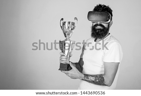 Man with long beard happy about his victory in online games tournament, gaming concept. Cheerful bearded champion holding golden cup. Nerdy bearded man in VR headset isolated on gray background.