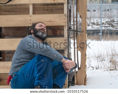 Man with long greying beard wearing wet grubby clothes sits hugging knees with a hopeless defeated expression in a wintry industrial urban setting with snow on the ground