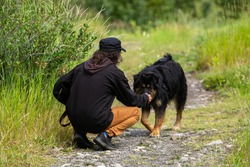 Man with long hair and black hat and jacket shot from behind, kneeling to pet his big black bernese looking dog during a walk in a mountain trail.