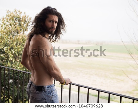 Man with long hair on a roof #1046709628