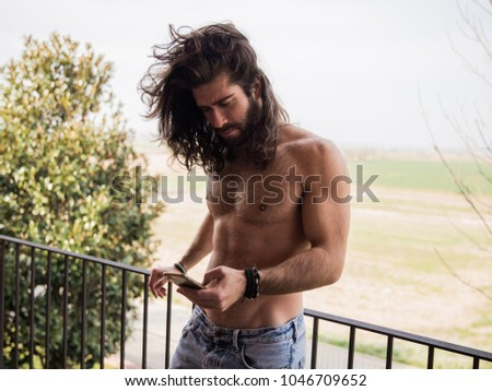 Man with long hair typing with the mobile #1046709652
