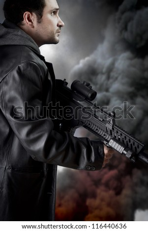 Man with long leather jacket and assault rifle, black smoke background