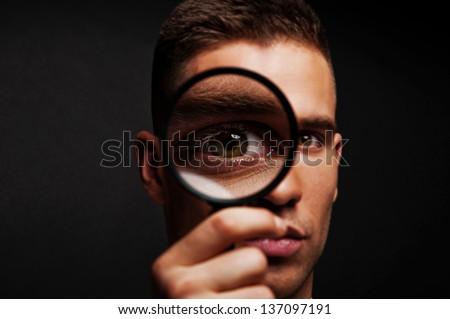 Man with magnifier on dark background