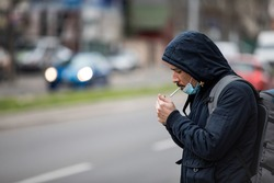 man with mask during COVID-19 pandemic smoking at the street