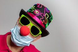 Man with medical mask, clown nose, sunglasses and colorful hat at carnival in covid-19 and corona times with copy space. Horizontal