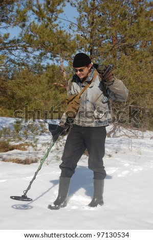 Man with metal detector in the forest at  early spring. Near Kiev,Ukraine