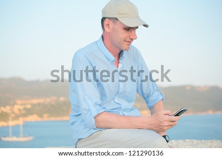 Man with mobile phone against a sea