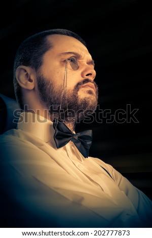 Man with Monocle and Bowtie Retro Portrait - Gentleman wearing monocle and bowtie, looking to the right side, retro portrait