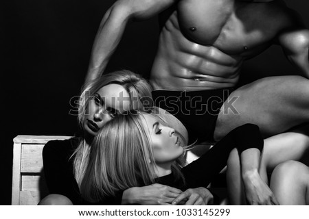 man with muscular wet body and strong athletic torso with sexy blonde twin girls in underwear pants and bodysuit on black background, lesbian and gay, homosexual seduction and foreplay, love relations
