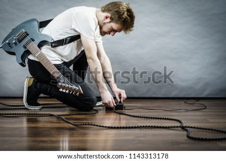 Man with musical instrument setting up guitar audio stomp box effects and cables in music studio