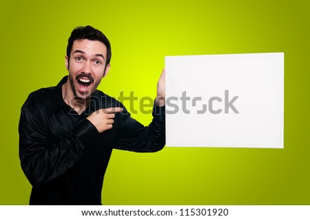 man with mustache and black jacket holding blank white board on yellow background - stock photo