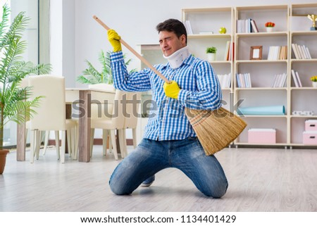 Man with neck unjury cleaning house in housekeeping concept #1134401429