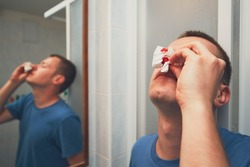 Man with nose bleed in bathroom. For themes of illness, injury or violence.
