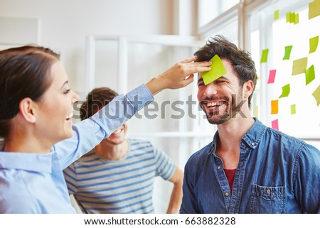 Man with note on forhead at creative workshop for team building