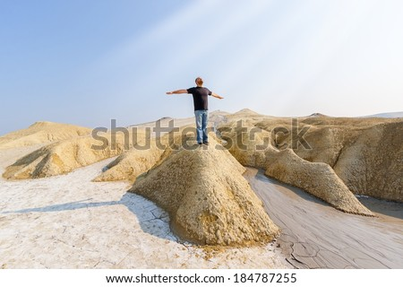 Man with open arms sitting on strange hill charging with the sun energy