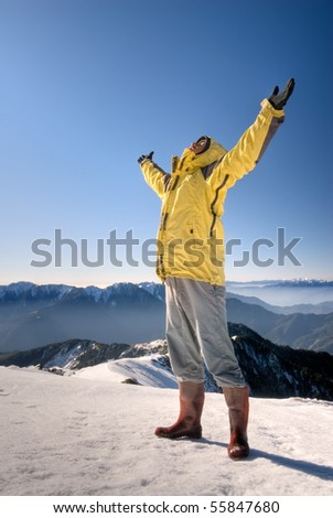Man with open arms stand on snow mountain top.