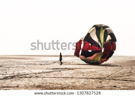 Man with open parachute after landing in a famous at Candolim Goa near Baga Beach and Vagator Beach. Yellow and blue wings slings are visible. Paragliding parachuting is extreme sport of recreation #1307827528
