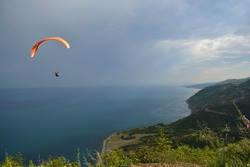man with orange parachute jumping off cliff