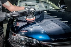 Man with orbital polisher in repair shop polishing car. Car detailing