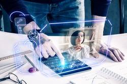 Man with pad leaning on desk at workplace and communicating with young woman via abstract futuristic screen hologram. Concept of network, communication, family, technology, augmented reality