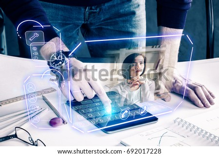 Photo of  Man with pad leaning on desk at workplace and communicating with young woman via abstract futuristic screen hologram. Concept of network, communication, family, technology, augmented reality