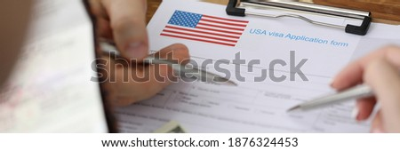 Man with passport and dollars points with pen at documents in folder of embassy closeup. Assistance in obtaining american visas concept. Сток-фото ©