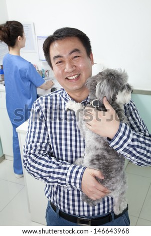 Man with pet dog in veterinarian\'s office