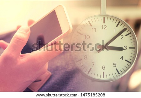 Man with Phone and Clock, business concept picture about deadline, delay and wasting life or time with mobile phone