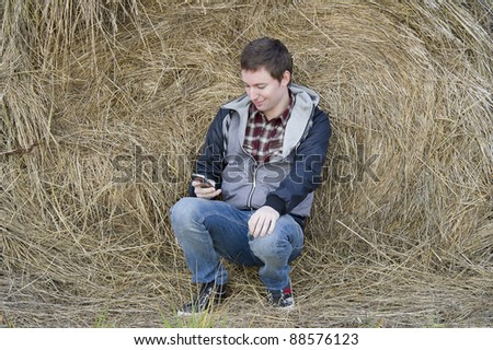 Man with phone sits near haystack