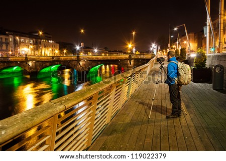 Man with photo equipment taking night shots of the river liffey in Dublin