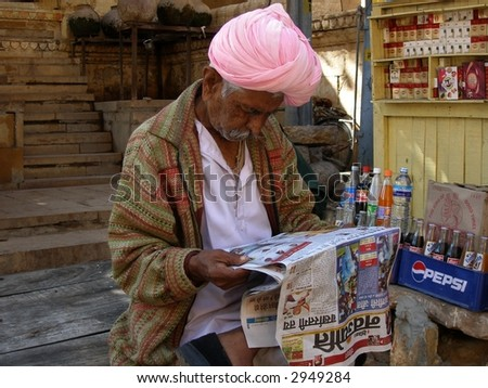 Man with pink turban reading newspaper
