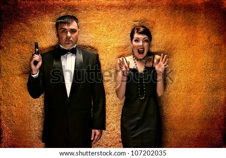man with pistol and woman about texture wall