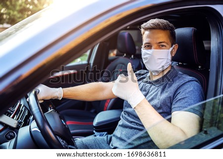 Man with protective mask and gloves driving a car. Infection prevention and control of epidemic. World pandemic. Stay safe showing thumbs up.