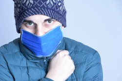 Man with protective mask and woolen hat. Close up of a Young man warm with medical mask against coronavirus. Covid-19 in autumn-winter.