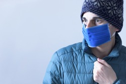 Man with protective mask and woolen hat. Young man warm with medical mask against coronavirus. Covid-19 in autumn-winter.