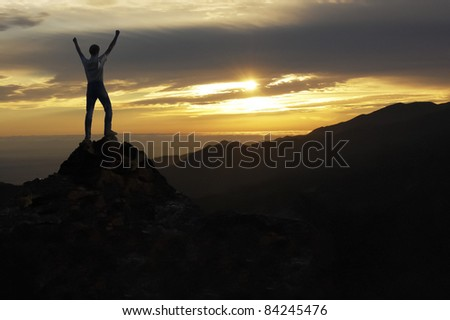 Man with raised arms on mountain peak