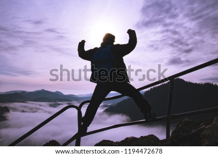 Man with raised arms on top of a surreal mountain, concept of inspiration, enthusiasm and aspiration #1194472678