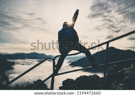 Man with raised hand on top of a mountain, concept of inspiration, enthusiasm and aspiration #1194472660