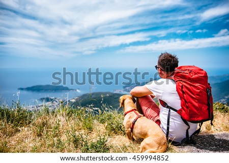 Man with red backpack and small yellow dog sitting on a mountain and looking at sea horizon