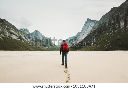 Man with red backpack walking alone at Horseid beach in Norway Travel lifestyle concept adventure outdoor summer vacations wild nature