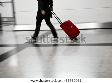 Man with red bags rushing at the airport