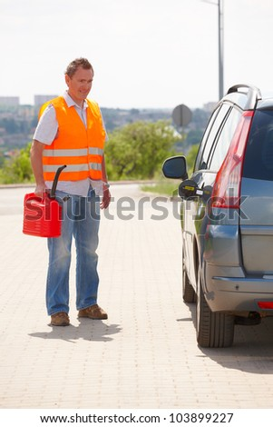 Man with red canister standing near his car