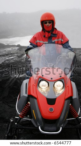 man with red helmet and scarf on red snowmobile wearing sunglasses