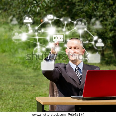 Man with red laptop in social networks outdoors, push the button - stock photo