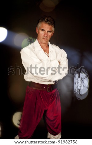 man with red pants standing over lights